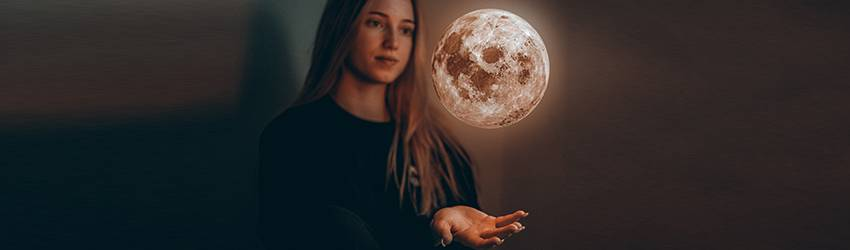 A woman holds a Full Moon in her hands in a dark room.
