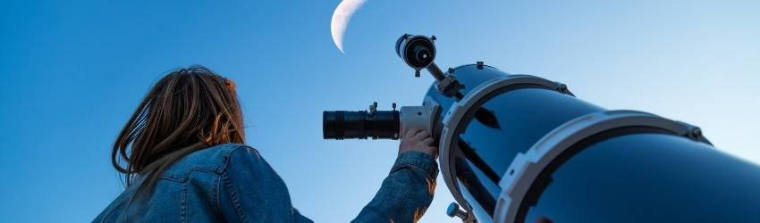 A person using a telescope to look at the Moon.