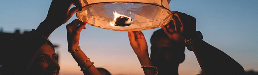 Four people release a paper lantern into the sky to celebrate the solstice.
