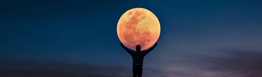 A man raises his arms in the sky so that it looks like he is holding the Moon on his shoulders.