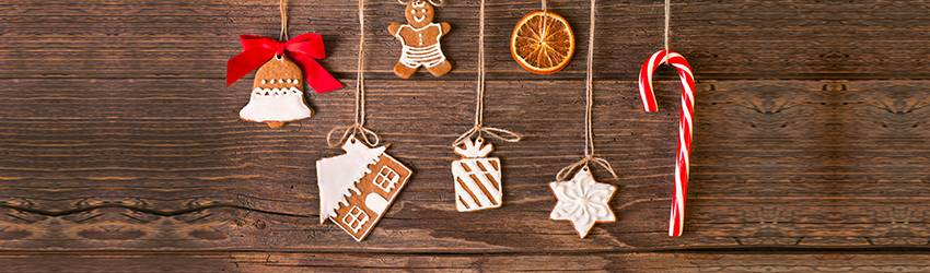 Holiday treats handing on strings in front of a wooden background.