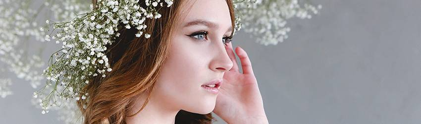 A woman wearing a tiara made of baby's breath flowers. She is the embodiment of a modern goddess.