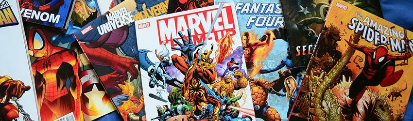 Marvel comics piled on top of a table.