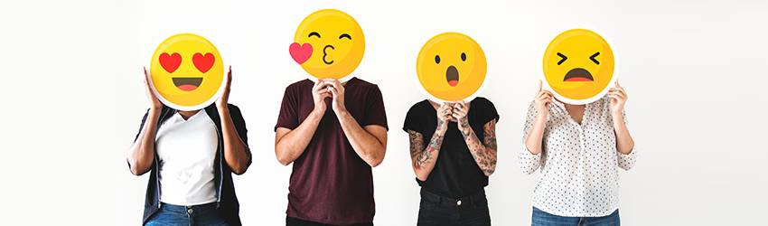 People standing with emojis in front of their faces.