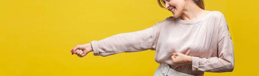 woman against yellow background punching the air with a smile