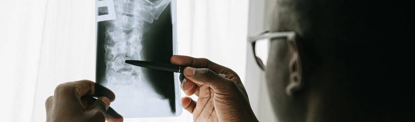 A doctor looks at an x-ray and points to a spot with a pen.