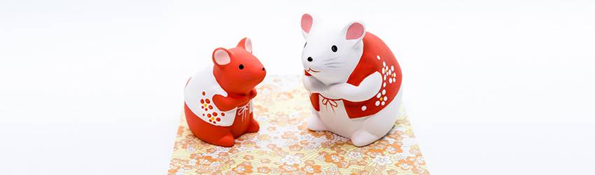 Two rat statues face each other. One is white and wearing a red vest, another is red and wearing a white vest.