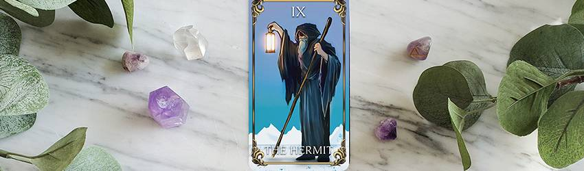The Hermit Tarot card laid above other Tarot cards.