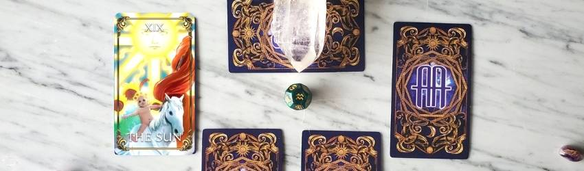 The Sun Tarot card is pulled next to a spread of face-down Tarot cards.