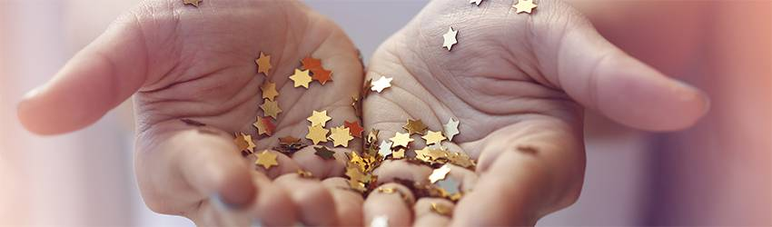 A person holds a bunch of gold star glitter confetti in their hands.