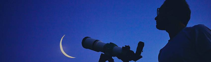 A man looks through a telescope at the New Moon in Pisces.