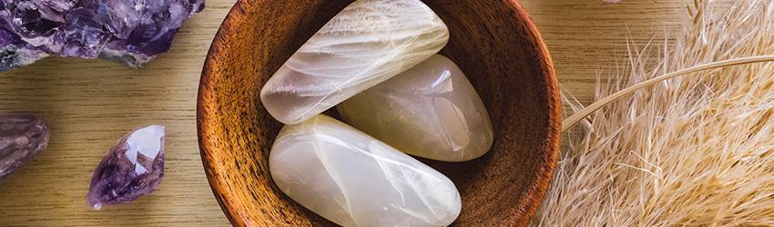 Moonstone in a bowl surrounded by Amethyst crystals.