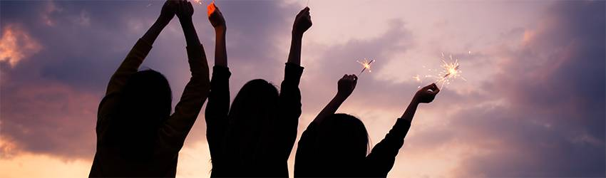Three people celebrate with sparklers in front of a purple and pink sky.