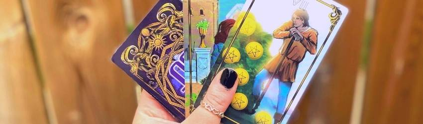 A person holds tarot cards in their hand.