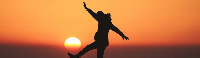 A woman balances on a fence in front of the sunset.