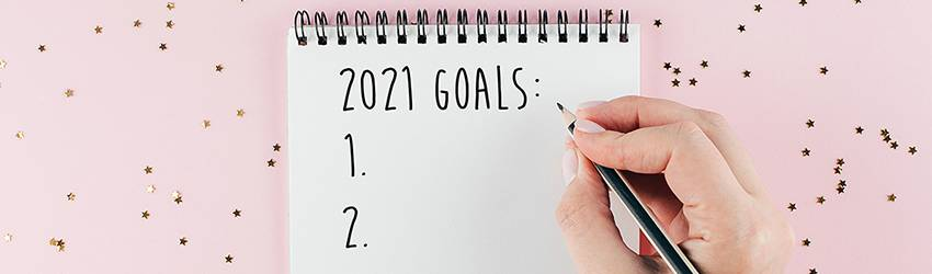 A person is writing down their new years resolutions on a notepad that reads