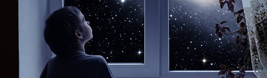 A child looks up at the stars through his bedroom window.