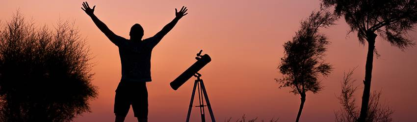 Man looking at the sunset with a telescope.