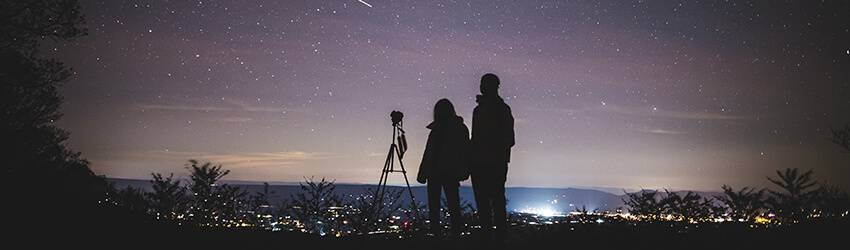 Two silhouetted people star at the stars next to a telescope.