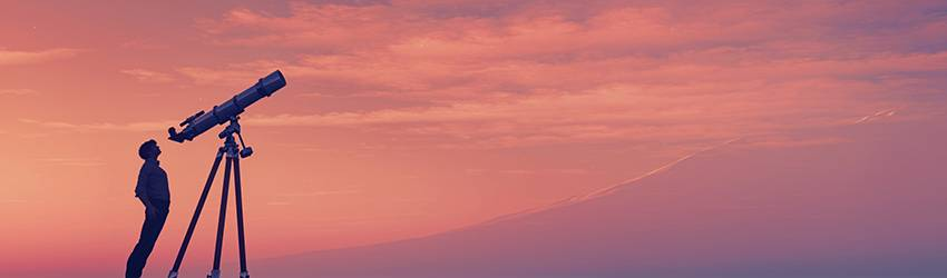 A person looks through a telescope into a pink and orange sky.