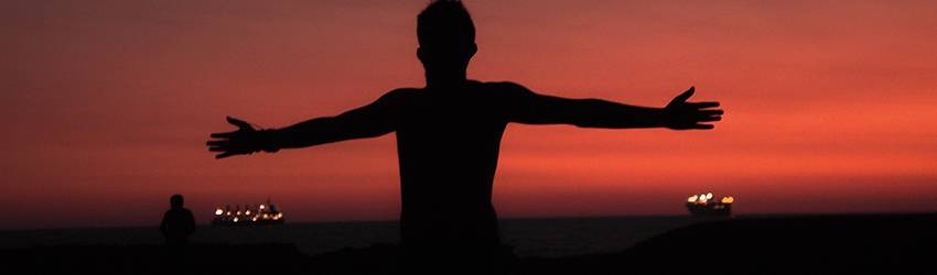 Person standing in front of a pinkish red sunset with their arms open.