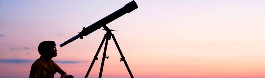 Man looks through a telescope at the horizon.