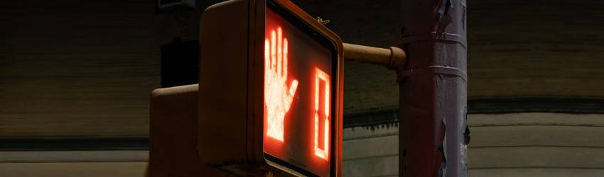 A walk light shows a red hand and the number zero at night.
