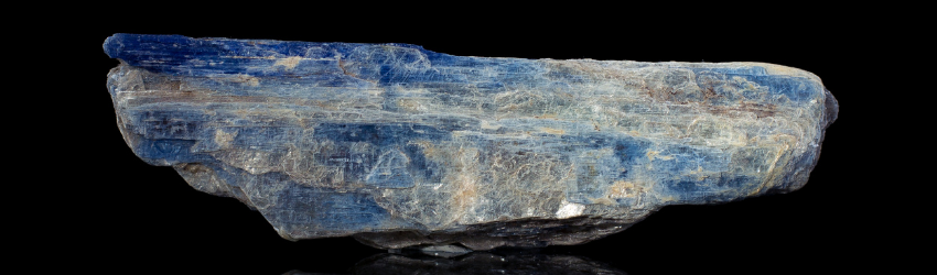 A shard of kyanite sitting on a black background and mirrored table.