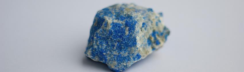 A raw chunk of Lapis Lazuli on a grey background.