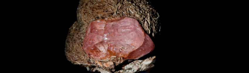 A pink morganite crystal sitting on a rock.