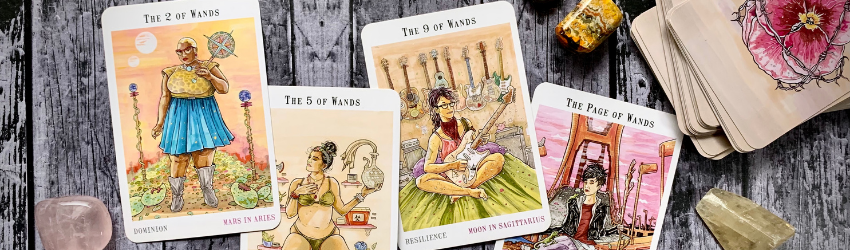Four tarot cards sitting on a wooden table.